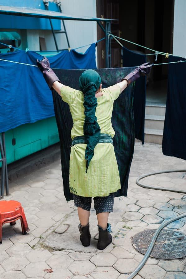 Femme népalaise en train d'étendre du tissus de chanvre pour séchage