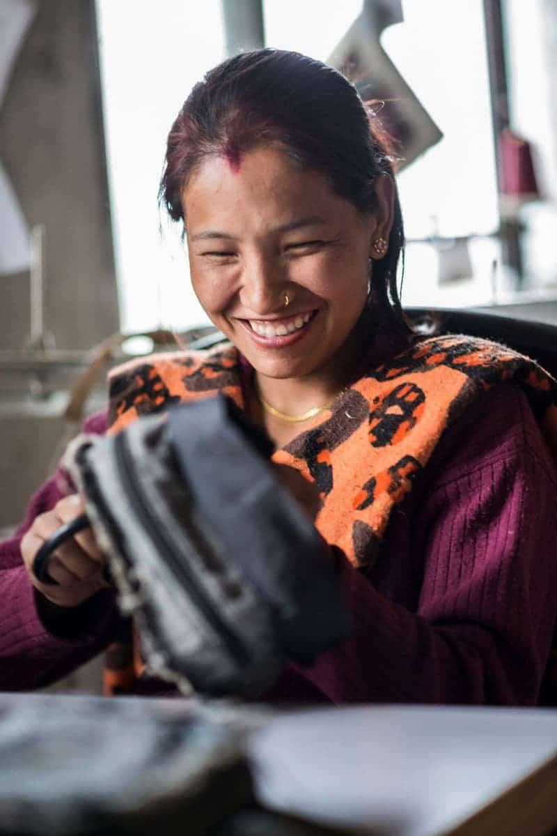 Femme népalaise réalisant un sac à dos