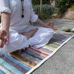 Femme pratiquant le Kundalini Yoga sur un tapis de yoga upcyclé
